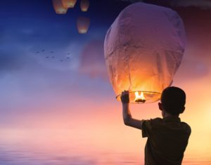 Young boy holds a lit lantern in the evening
