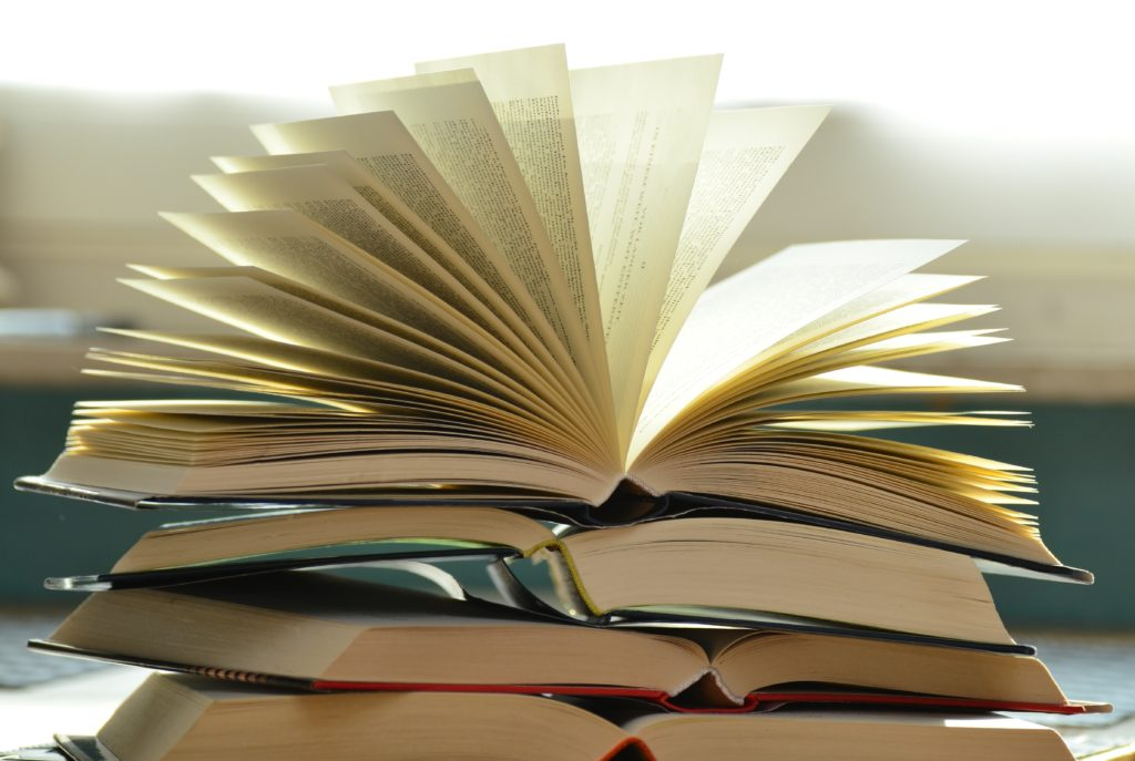 An image of a stack of books with one open book.