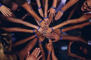 many hands reaching toward each other, blue bracelets