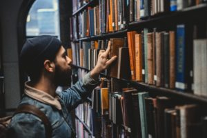 young man with beard and beanie standing in front of library shelf, picking out one book