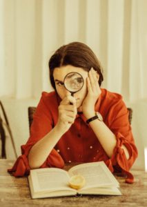 woman in red blouse holds magnifying glass in front of her while reading a book