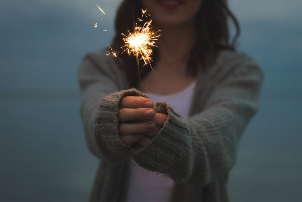 woman holding sparkler in hands