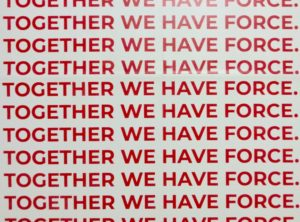sign with multiple lines spelling the phrase 'together we have force' in red
